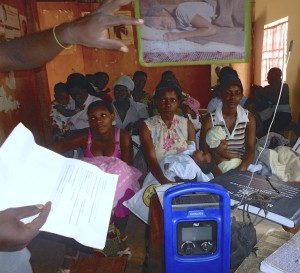 Women at the health center listening to a life player and asking questions